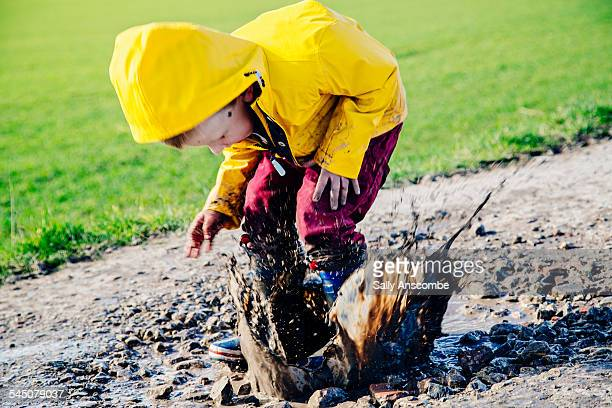 Child jumping in a muddy puddle