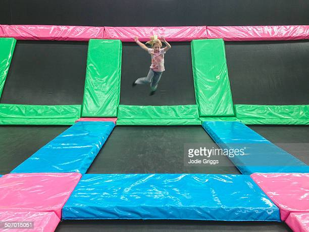 Child jumping in air at indoor trampoline centre