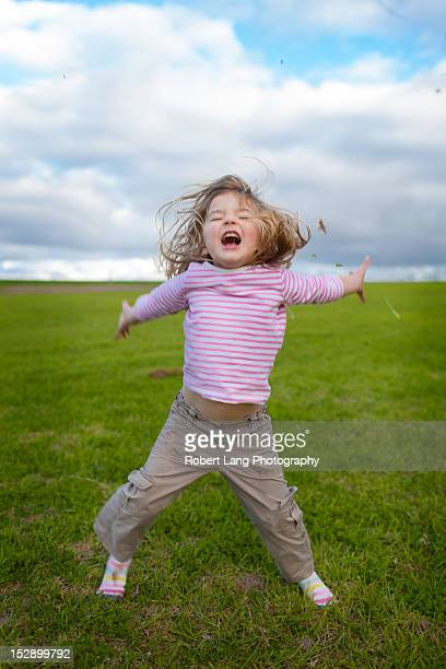 Child jumping in air, throwing grass, Australia