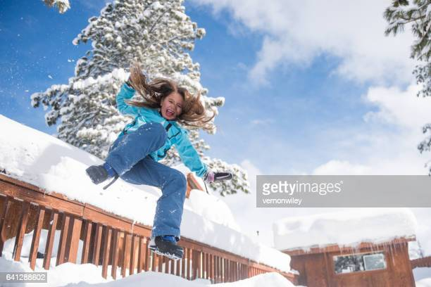 Child jumping off porch into snow