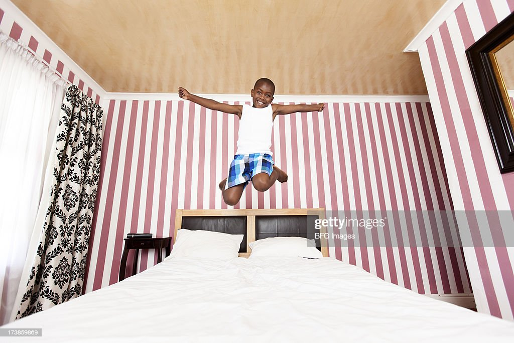 Child jumping on bed : Stock Photo