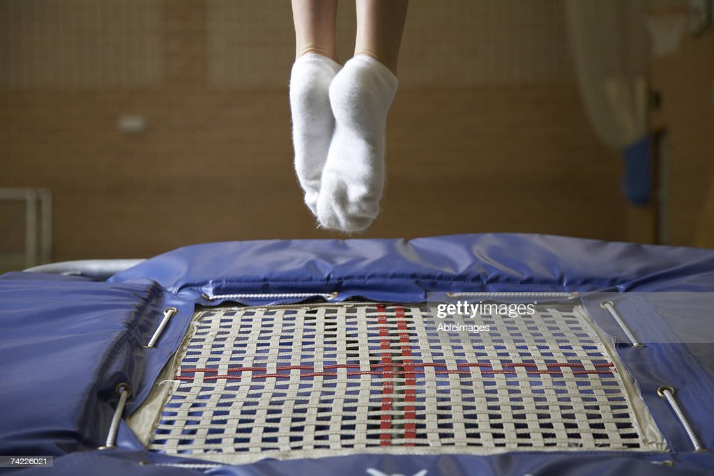 'Child (11) jumping on trampoline, low section' : Stock Photo