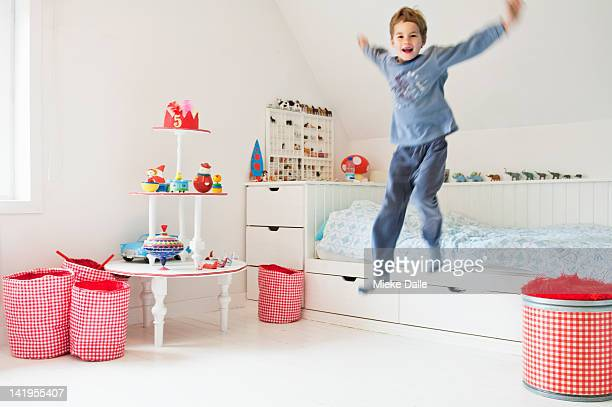 child jumping out of bed in bedroom