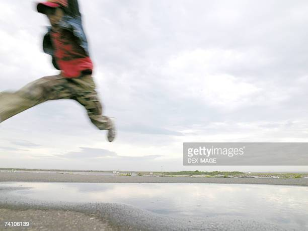 Child jumping over water