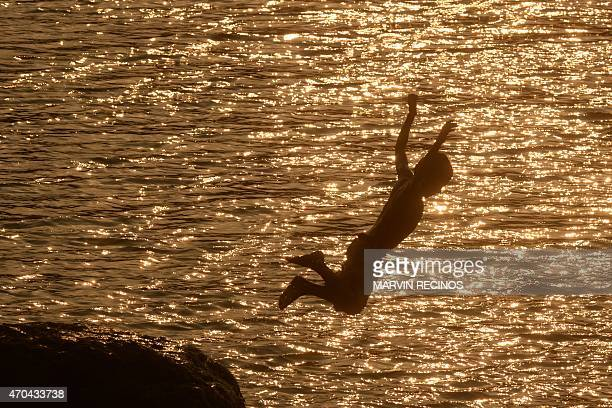A child jumps into the waters of Lake Suchitlan at sunset in Suchitoto 47 km east of San Salvador El Salvador on April 19 2015 AFP PHOTO/ Marvin...
