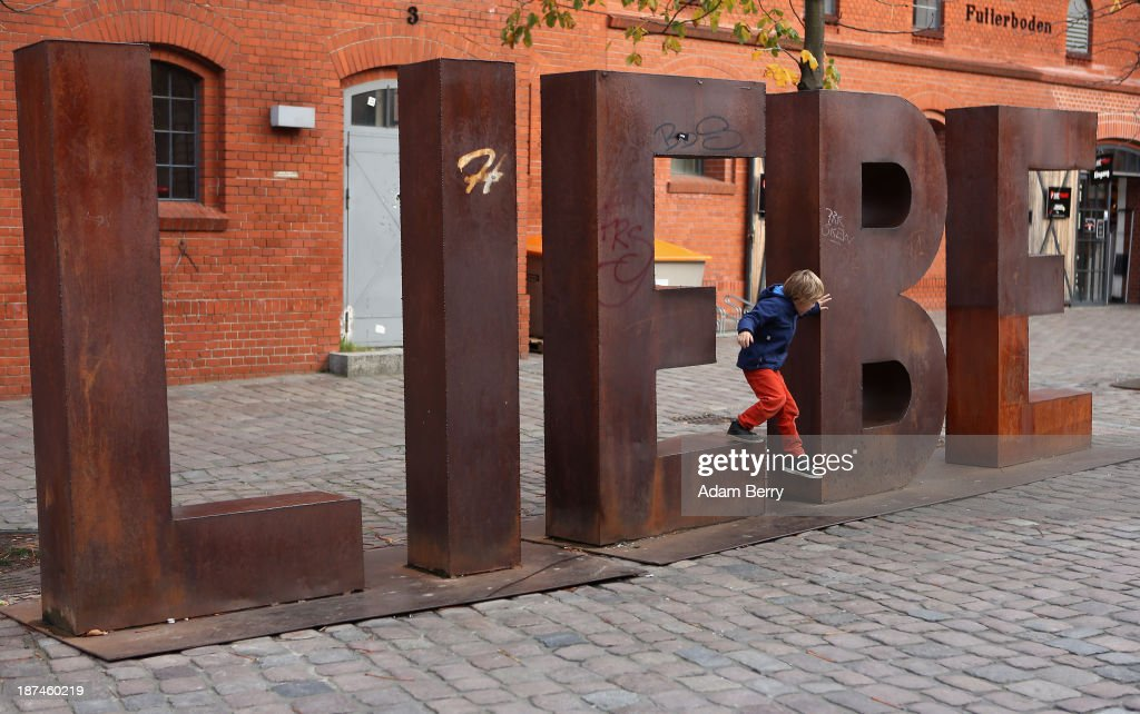 A child jumps off a sculpture presenting the word 'Liebe,' or 'Love,' at a site in an old brewery complex known as the Kulturbrauerei, used during World War II to shoot defectors from the German army, on the 75th anniversary of Kristallnacht, or the 'Night of Broken Glass' on November 9, 2013 in Berlin, Germany. The word Kristallnacht is used to refer to a series of violent antisemitic pogroms that occurred prior to World War II on November 9-10, 1938, throughout Germany, annexed Austria, and in areas of the occupied Sudetenland in Czechoslovakia.