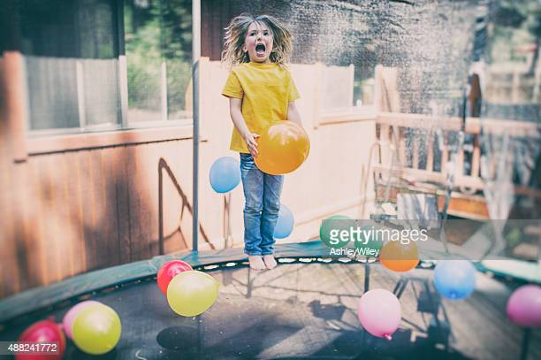 Child jumps on trampoline laughing with balloons