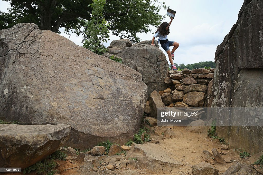 A child jumps onto a stone wall at 'The Home of a Rebel Sharpshooter' on July 2, 2013 in Gettysburg, Pennsylvania. Many tourists visiting the historic site pose for photos there as part of their battlefield experience. The original photo featured a dead Confederate soldier in a photo taken by Alexander Gardner on July 5, 1863. The photograph was later discovered to be staged, the dead body of the 'sharpshooter' having been brought from another place on the battlefield for the photograph.