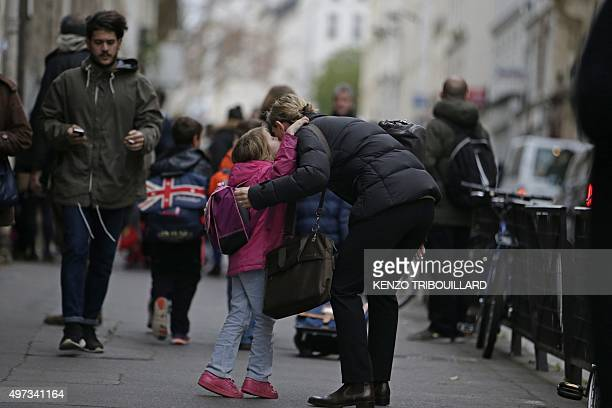 A child kisses a relative before going to school early on November 16 2015 in Paris three days after the terrorist attacks that left over 130 dead...