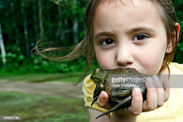 Child kissing frog