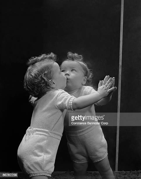 Child kissing her reflection