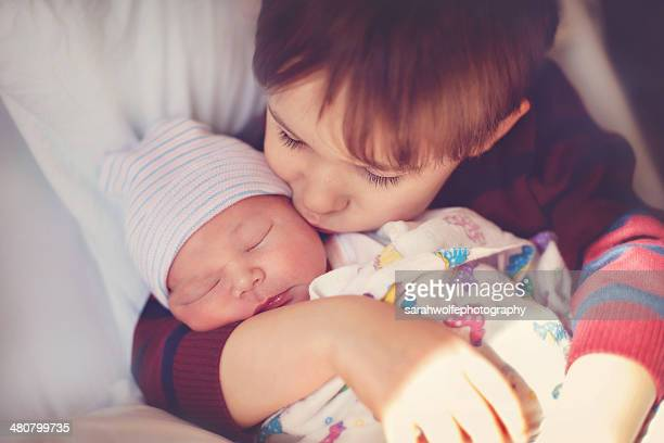 child kissing newborn in hospital