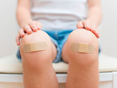 Child knee with an adhesive bandage.