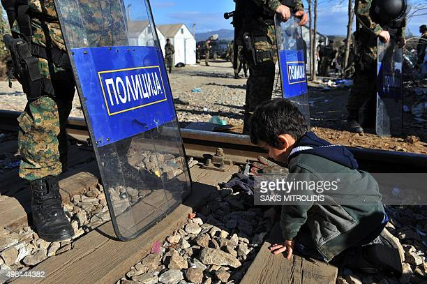 A child kneels on railway tracks before Macedonian border police as migrants and refugees wait to cross the border of Greece and Macedonia near...