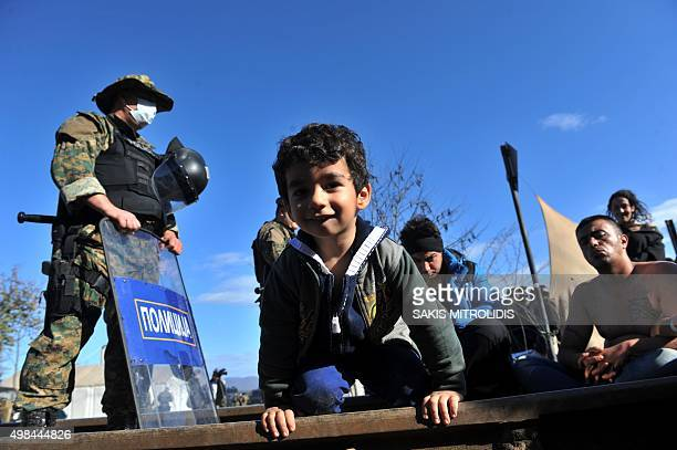 A child kneels on railway tracks between Macedonian border police and migrants and refugees claiming to be from Iran with their mouths sewn shut who...