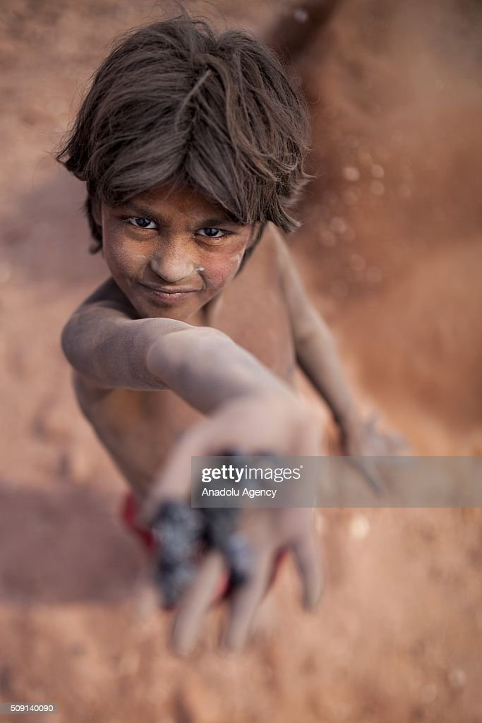 Child labor show coals in his hand near brick making field in Dhaka, Bangladesh on February 09, 2016. Despite of the hazardous effect of dust on health, child labor collect coal and sell it around $4 per a week to help their family budget. Child labor in Bangladesh is around 30.1%. Bangladesh adopted the National Child Labor Elimination Policy at 2010, providing a framework to eradicate all forms of child labor by 2015, but according to the International Labor Organization there are still around 3.2 million child labors in Bangladesh.