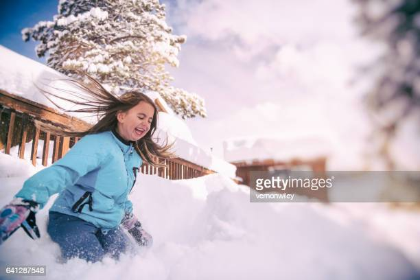 Child landing in a large pile of snow