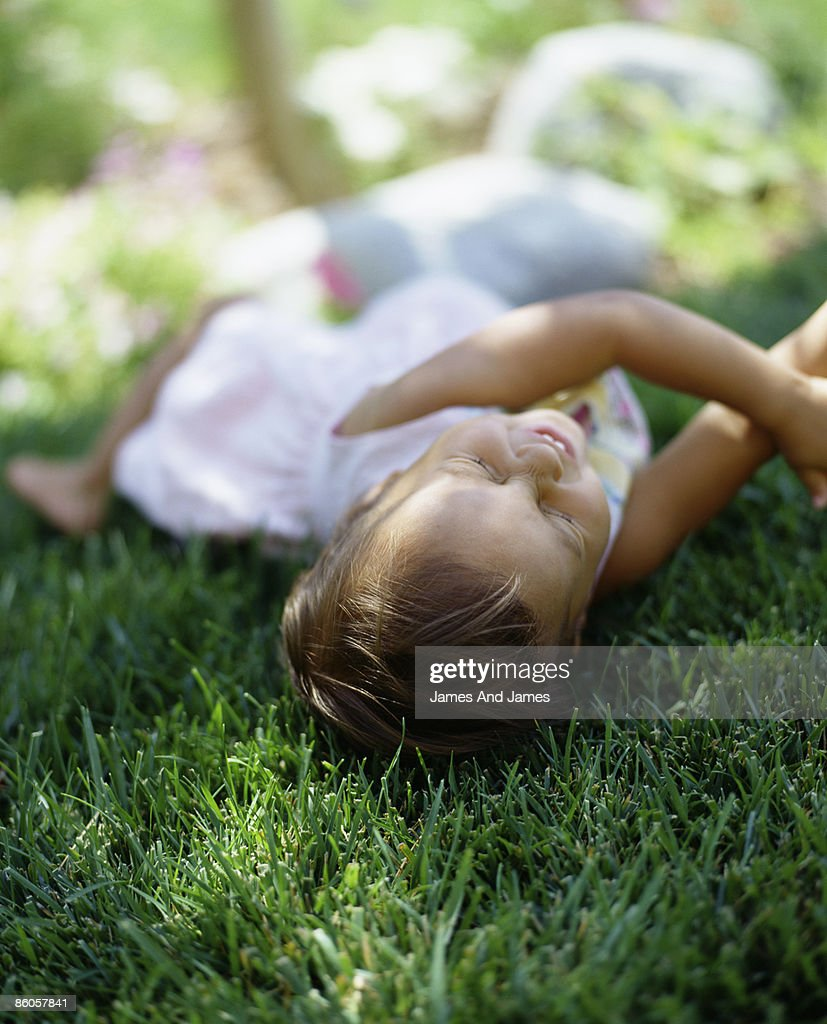 Child laughing on grass : Stock Photo