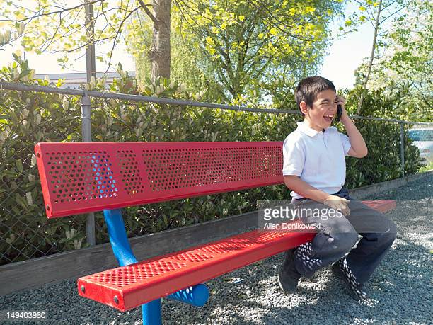Child laughing while talking on phone on bench