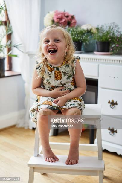 Child laughing with a lollipop in her mouth