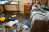 Child lays in bed using a tablet and headphones. Bedroom is very messy.