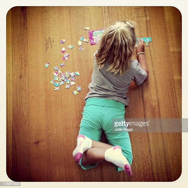 Child laying on wooden floor doing jigsaw puzzle