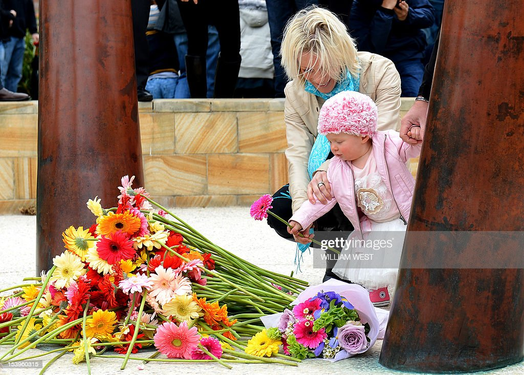 A child lays a flower after a ceremony to commemorate the 10th anniversary of the 2002 Bali attacks, at a memorial dedicated to Australians killed in the attacks, at Coogee Beach in Sydney on October 12, 2012. Survivors and relatives of the dead flocked to emotional Bali bombing ceremonies across Australia on October 12, with Foreign Minister Bob Carr praising the nation's mature response to the atrocity. AFP PHOTO/William WEST