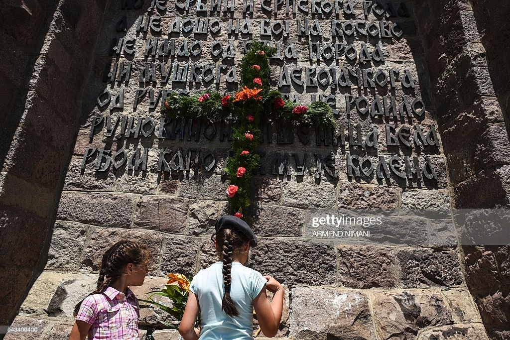 A child lays flowers the Gazimestan memorial, near the village of Mazgit, Kosovo, as people take part in a ceremony marking the historic 'Battle of Kosovo' on June 28, 2016. The ceremony marks the Battle of Kosovo in 1389 when the Serbian army was defeated by the Ottoman Empire. / AFP / ARMEND