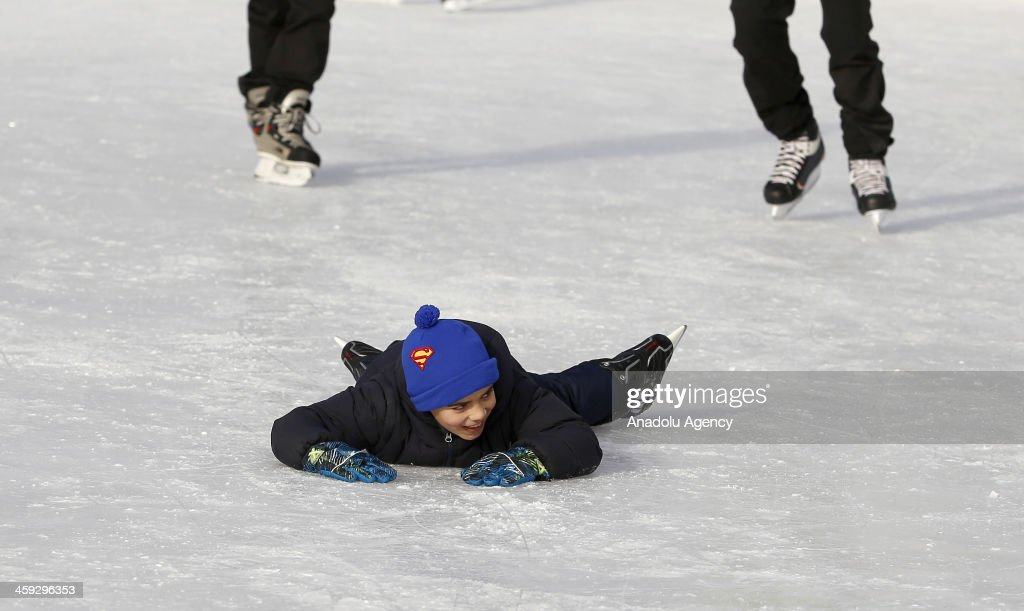 A child lays on the ice after falling down at the McCarren Park pool in New York,United States on December 24,2013. after McCarren park pool converted to an ice skating area. Pool hosts 800 visitors everyday, without regard to cold weather American people have fun in McCarren park pool in New York,United States,on December 24,2013.