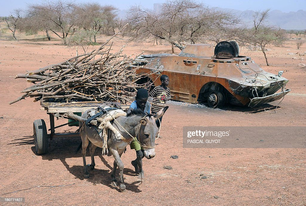 A child leads his wood filled donkey cart past a destroyed Malian army armoured vehicle on February 5, 2013 in Douentza. The town was retaken by French and Malian troops in January. AFP PHOTO / PASCAL GUYOT