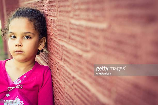 A child leaning against a red brick wall