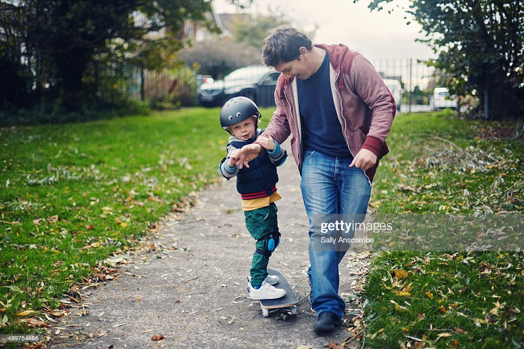 Child learning to skateboard : Stock Photo