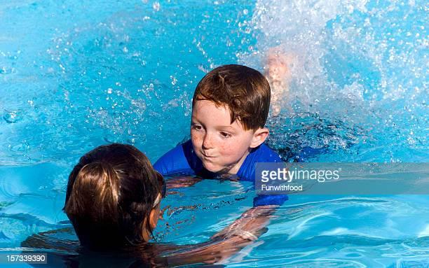 Bambino imparare a nuotare, ragazzo di nuoto in piscina Istruttore &
