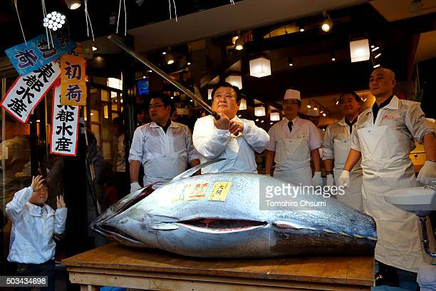 A child left looks on as Kiyomura KK President Kiyoshi Kimura center poses with a fresh bluefin tuna at one of the company's Sushi Zanmai sushi...