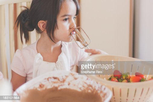 A child licking the whisks from a hand mixer