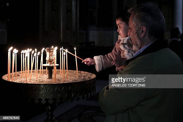 A child lights a candle during Orthodox Easter celebrations at a church in the center of Athens on April 11 2015 Millions of Greeks flock to churches...