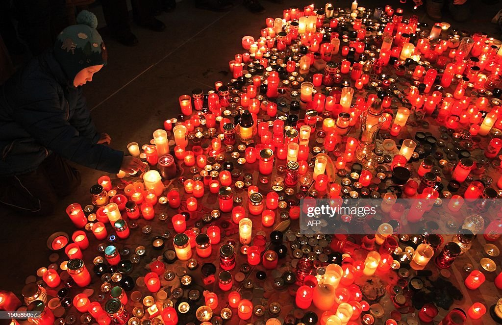 A child lights candles at Narodni street where in 1989 students clashed with the communist police on November 17, 2012 in Prague. Some twenty thousand people protested today against the government of the Czech Republic.