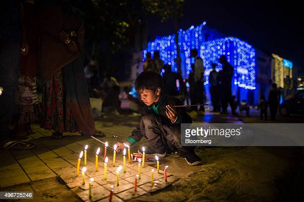 A child lights candles during Diwali celebrations in Delhi India on Wednesday Nov 11 2015 Diwali the Hindu Festival of lights sees shops and homes...