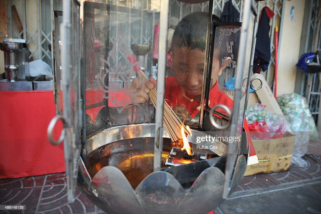 A child lights incense at a shrine in Chinatown during festivities welcoming in the Chinese New Year on January 31, 2014 in Bangkok, Thailand. Despite a government declared state of emergency and ongoing anti-government protests in the run-up to the general election on February 2nd, festivities were held in Bangkok's Chinatown ushering in the Chinese New Year.