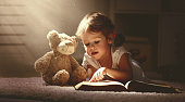 child little girl reading a magic book in the dark home with a toy teddy bear