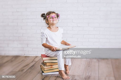Child little girl sitting on a stack of books with glasses : Stock Photo