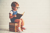 happy child little girl with glasses reading a books