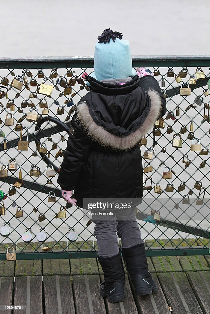 A child look at padlocks on the Pont des Arts on January 4, 2013 in Paris, France. The nine-arch metallic footbridge completed in 1804 is one of the most romantic places of the capital where people visit it to attach love padlocks illustrated with their initials or messages of love, before throwing the key into the River Seine. The bridge is also a meeting place for artists who find inspiration from the surrounding views of the city.