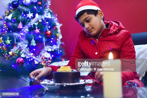 Child Looking at Christmas Cake with Christmas Tree and Candle
