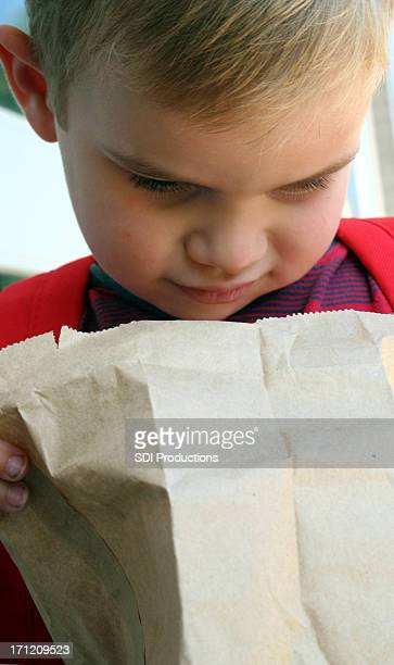 Child Looking Down Into An Open Paper Bag