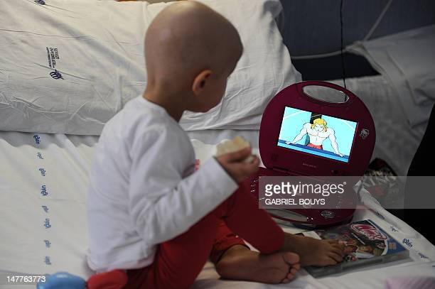 A child looks at a cartoon on his bed at the Bambino Gesu hospital on March 23 2012 in Rome The Bambino Gesu hospital is specialized in the treatment...