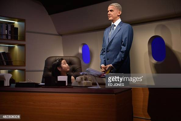 A child looks at a waxwork model of US President Barack Obama on the opening day of the first Asian outpost of France's famous waxwork museum Musee...