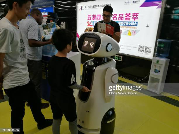A child looks at an AI service robot during the 122nd Canton Fair on October 15 2017 in Guangzhou Guangdong Province of China The 122nd Canton Fair...