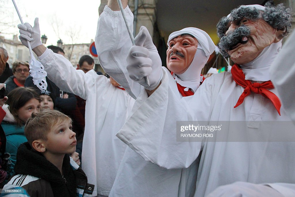 A child looks at masked people performing in the historical centre of Limoux, southern France, on January 6, 2013, as they take part in the city's carnival, which started on January 6 and will end on March 17. AFP PHOTO / RAYMOND