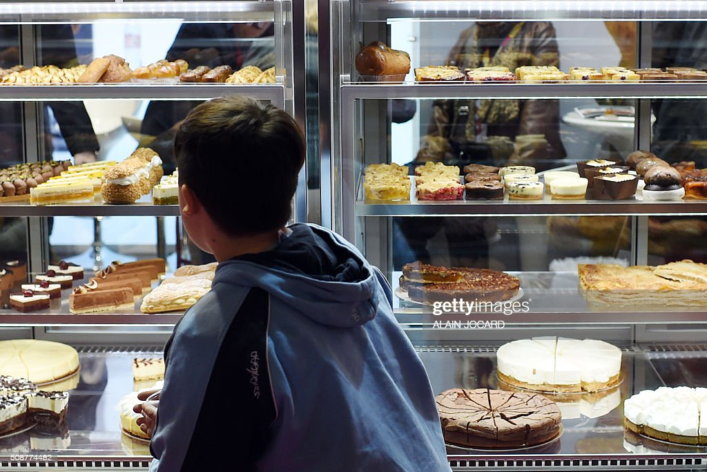A child looks at pastry on the 'La compagnie des desserts' stand, during the Europain fair, on February 6, 2016, in Villepinte near Paris. / AFP / ALAIN JOCARD